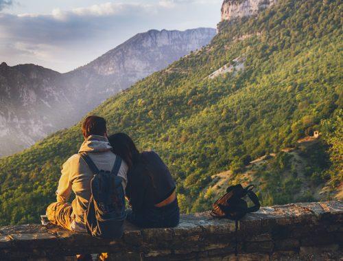 Couple l'un contre l'autre devant un paysage de montage verdoyante.